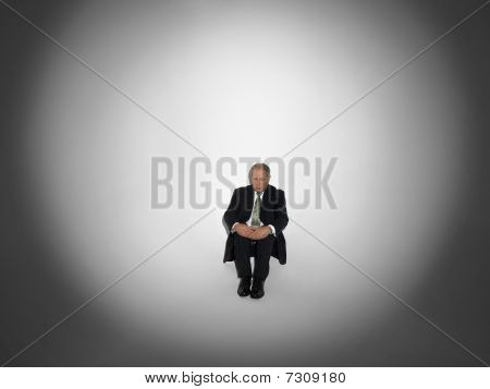 Businessman sitting under Spotlight