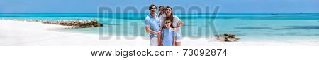 Happy beautiful family on a beach during tropical vacation, wide panorama perfect for banner