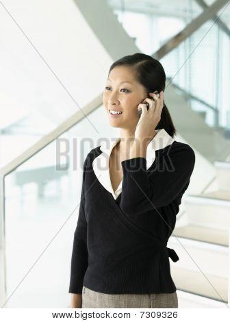 Sonriendo empresaria de pie hablando por móvil