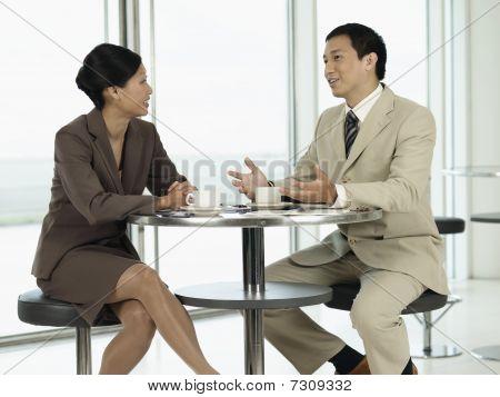 Постер, плакат: Бизнесмены сидя за столом разговаривали друг с другом, холст на подрамнике