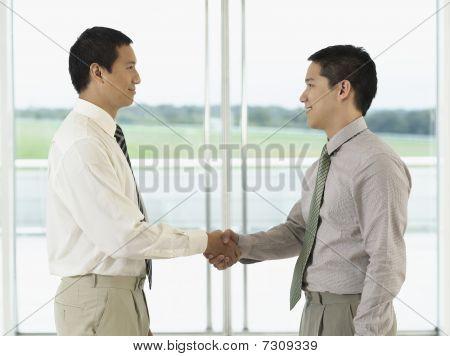 Businessmen standing Shaking Hands in front of window profile