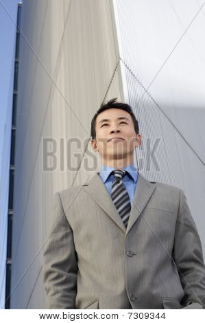 Young Businessman standing hands in pockets low angle view