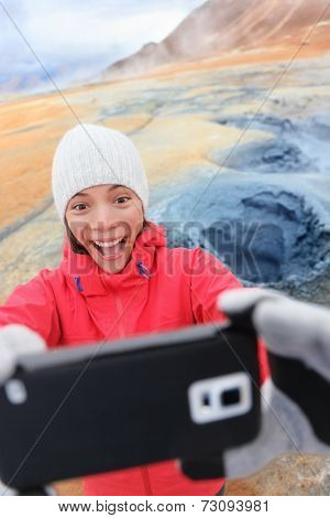 Iceland tourist taking selfie photo with smartphone camera at landmark destination: Namafjall Hverarondor hverir mudpot also called mud pool hot spring or fumarole. Woman having Icelandic nature.