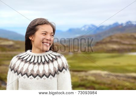 Woman on Iceland in Icelandic sweater. Portrait of girl happy smiling outdoors in nature wearing Icelandic sweater. Pretty Asian Caucasian multiracial female model