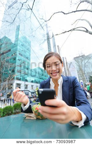 Young business woman on smartphone eating salad on lunch break in City Park living healthy lifestyle working on smart phone. Happy multiracial businesswoman, Bryant Park, manhattan, New York City, USA