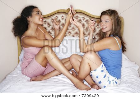 Teenage Girls sitting legs crossed on bed looking in compacts applying make-up side view