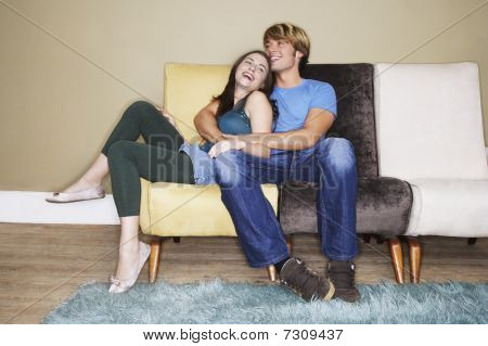 Young couple sitting hugging laughing on sofa