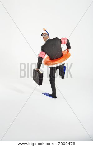 Middle-aged Businessman In Flippers, Inflatable Rubber Ring, Snorkel And Goggles Waddling, Carrying