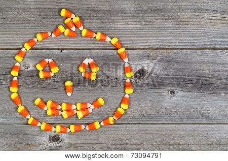 Candy Shaped As Halloween Pumpkin On Rustic Wood