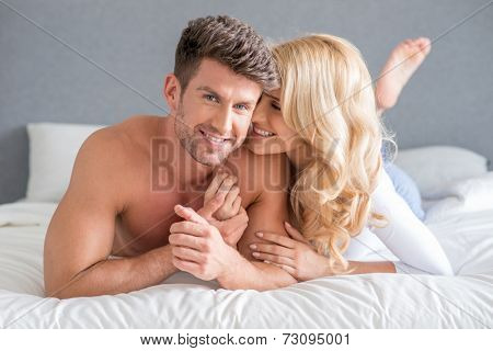 Sexy Sweet Young Couple Lying on White Bed Fashion Shoot. Isolated on Gray Background.