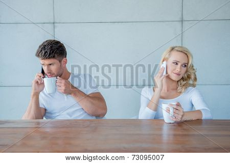 Couple both using their mobile phones simultaneously as they sit at a wooden counter enjoying their morning coffee