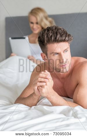 Handsome man with a displeased expression lying on his bed looking off to the side with a frown because his wife is ignoring him to read on her tablet-pc