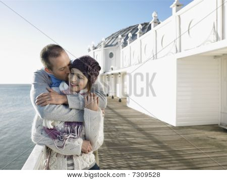 Man kissing woman standing on pier half length
