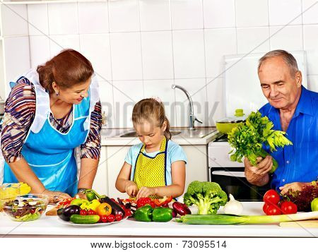 Family with child cooking at kitchen. Grandfather and grandmother.