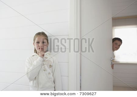 Girl with finger on lips standing by boy peeking round door