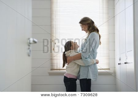 Mother and daughter hugging standing in front of window