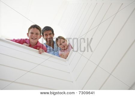 Father with son and daughter looking over white wall view from below