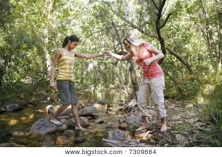 Two teenage girls (16-17) years crossing stream holding hands
