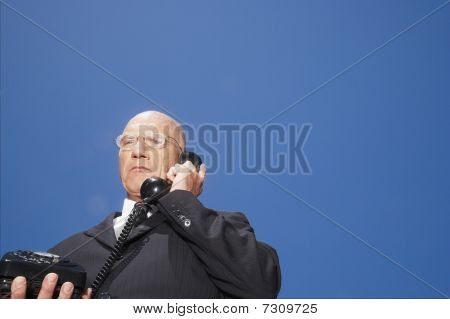 Busieness man using phone standing against sky low angle view