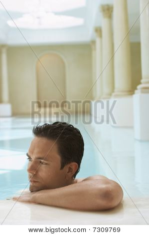 Young man leaning on edge of swimming pool portrait