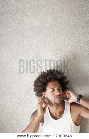 Young Man Leaning Against Wall Listening To Music Through Headphones, Portrait