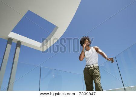 Joven utilizando el teléfono móvil en vista de ángulo bajo de retrato de balcón