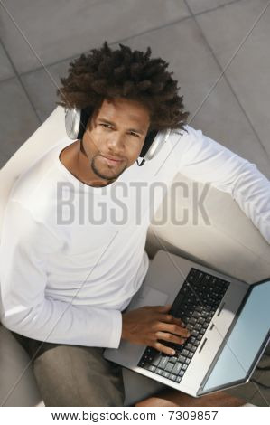 Young man sitting on sofa on laptop