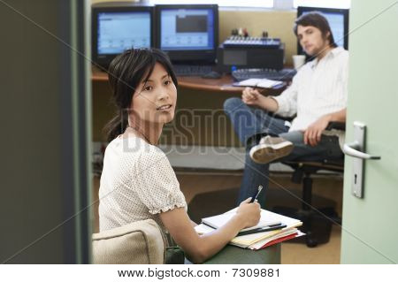 Two Office workers having meeting woman taking notes.