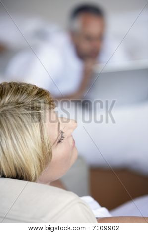 Woman relaxing sitting in armchair in bedroom elevated view