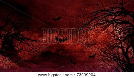 Grunge Halloween landscape with spooky trees and bats against a moonlit sky