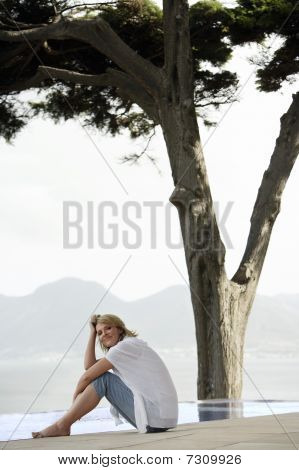 Woman sitting on floor by infinity pool side view