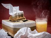 image of tissue box  - Tissue box in knit encasement and hot flu medicine drink over dark red background - JPG