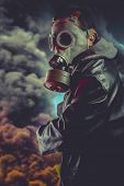 stock photo of rubber mask  - Armed man with gas mask over explosion background - JPG