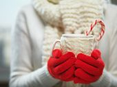 Woman holding winter cup close up on light background. Woman hands in woolen red gloves holding a cozy mug with hot cocoa, tea or coffee and a candy cane. Winter and Christmas time concept. poster