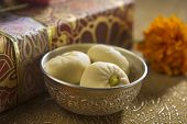 stock photo of bangla  - A bowl of an Indian sweet along with gift box in the background - JPG