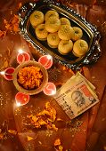 stock photo of mithai  - worshiping Indian currency notes as a god of wealth during Diwali Festival - JPG