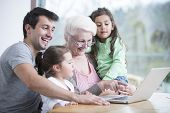 foto of three sisters  - Happy three generation family using laptop at table in house - JPG