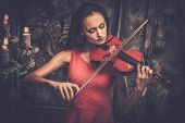 stock photo of mystical  - Young woman in red dress playing violin in mystic interior  - JPG