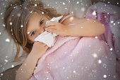 picture of blanket snow  - Composite image of girl suffering from cold as she lies in bed against snow falling - JPG