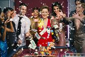 stock photo of roulette table  - People throwing chips and cash on roulette table against snow falling - JPG