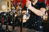 Composite image of Barkeeper pulling a pint of beer against snow falling poster