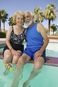 Senior Couple sitting on edge of swimming pool portrait.