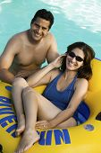 Couple in swimming pool woman lying on inflatable raft elevated view portrait.