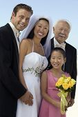 stock photo of mixed race  - Bride and Groom with father and sister outdoors  - JPG