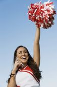 Smiling Cheerleader rising pom-pom talking on mobile phone (low angle view)