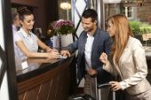 foto of receptionist  - Receptionist giving tourist information to hotel guests upon arrival - JPG