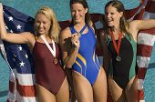 Three female swimmers celebrating victory by pool side