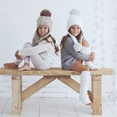 image of leg warmer  - Cute little girls of 5 years old wearing knitted trendy winter clothes posing over white brick wall - JPG