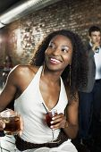 stock photo of african american hair styles  - Woman holding cocktail sitting in bar indoors  - JPG