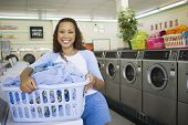 picture of laundromat  - Portrait of woman with basket of clothes in laundromat - JPG